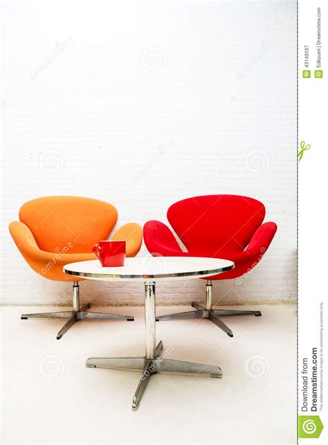 modern interior table with coffee cup and two chairs stock
