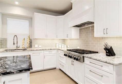 white kitchen with gray glass backsplash and granite