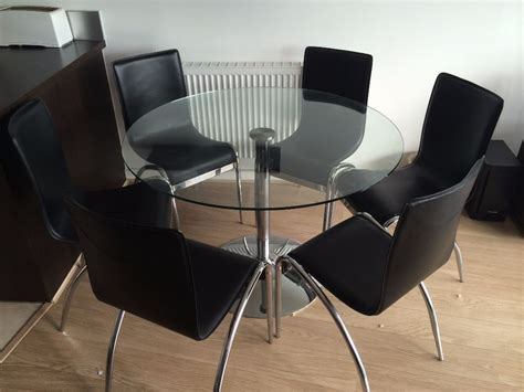 glass dining table and 6 matching black leather and
