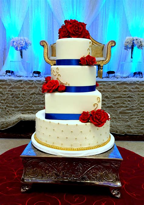 Royal blue, red, and gold cake. Top three tiers covered in ...