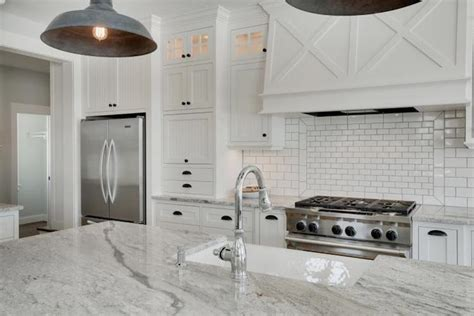 stainless steel stove and refrigerator white granite counters transitional kitchen