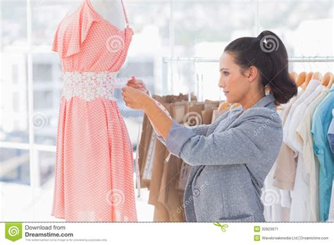 pictures of designer pretty fashion designer measuring dress on a mannequin
