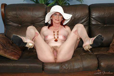 Glassed Black Haired Granny Stripping On The Armchair