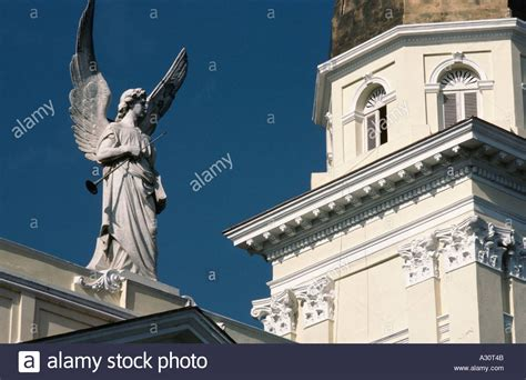 White Angel Statue Holding A Trumpet On Top Of An Old