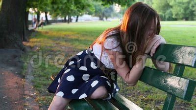 teenage girl upset  crying sitting   park bench