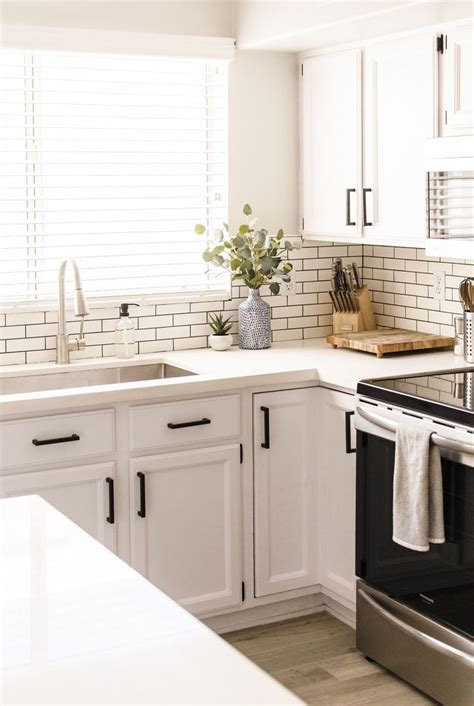 all white kitchen white subway tile with dark grout is