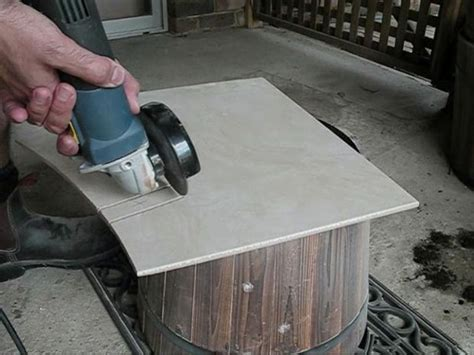cutting a curve in a ceramic tile with an angle grinder all