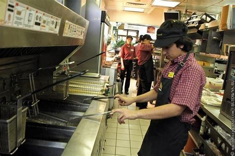 A worker in at the fryer .   McDonald's Office Photo