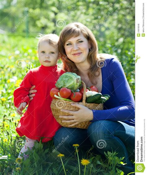 Happy Family With Vegetables In Garden Royalty Free Stock