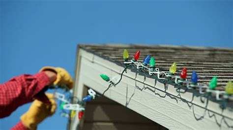 how to put christmas lights on roof man installing led christmas lights onto a house roof