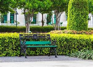 Green Bench in the Park with White Building Background ...