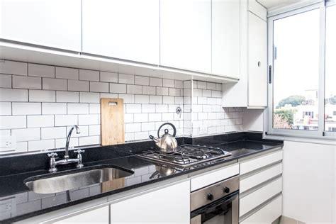 cocina de muebles blancos mesadas de granito negro
