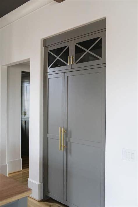 contemporary kitchen features  inset refrigerator  freezer clad  gray paneled doors