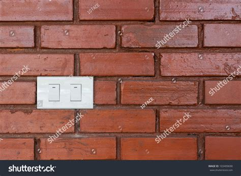 light switch on red brick wall 103409690