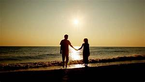 Girl and boy go holding hands from sea, silhouettes on ...