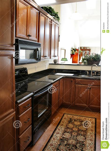kitchen wood cabinets black  stainless stove stock images image