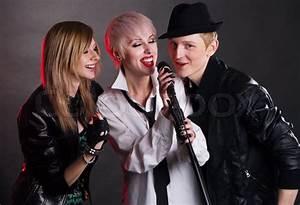 Teenage rock band against black background | Stock Photo ...