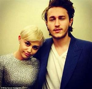 Miley Cyrus covers up in slinky silver gown to pick up two ...