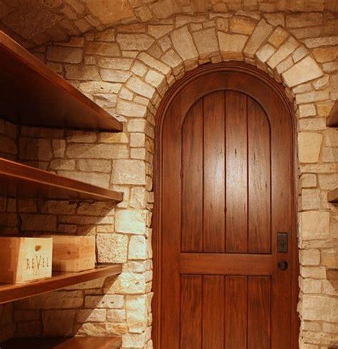 wine cellar door wooden shelving stone walls wine room