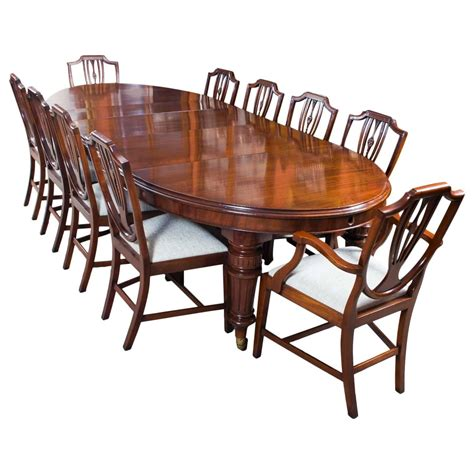 antique extending dining table with ten shield back chairs