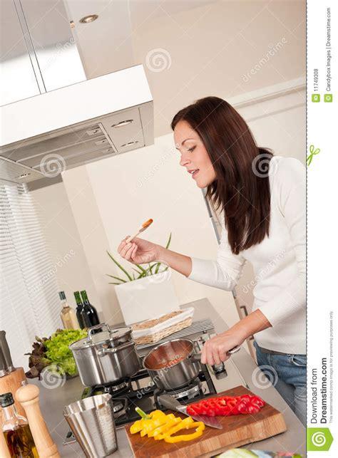 femme dans la cuisine femme heureuse faisant cuire la sauce tomate dans la