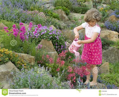 Cute Girl Watering Flower In The Garden Stock Image