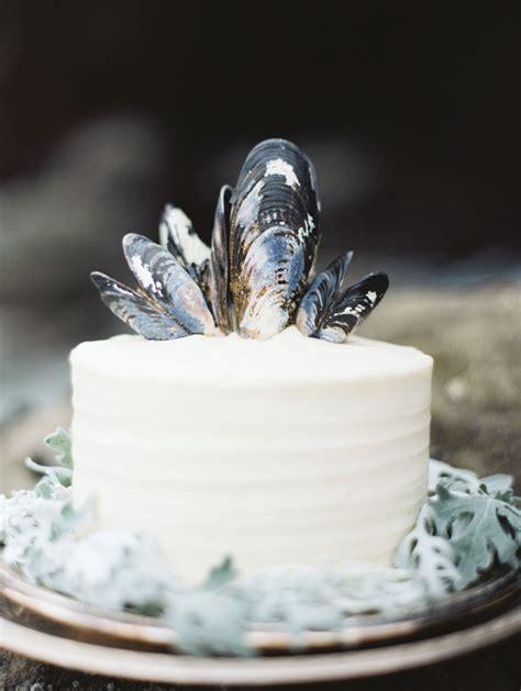 simple white wedding cake black blue mussel shell topper