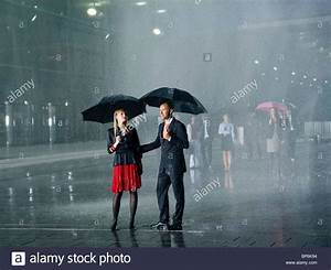 A couple standing in the rain under umbrellas Stock Photo ...