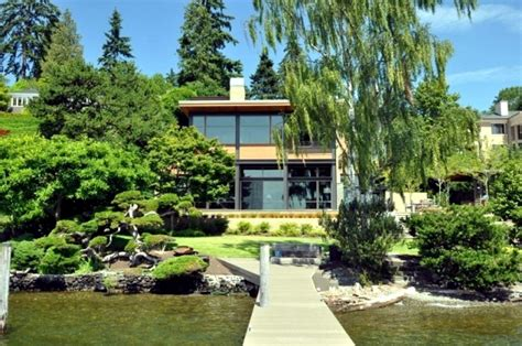open floor plan design modern house on the lake with a flat green roof and a