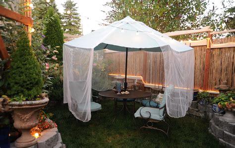 mosquito net draped a sea foam green umbrella and pat