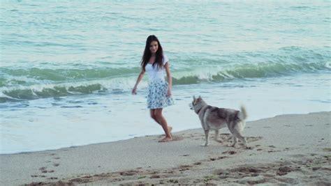 young female playing  siberian husky dog   beach