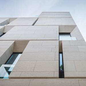 Angled window reveals and balconies interrupt the smooth ...