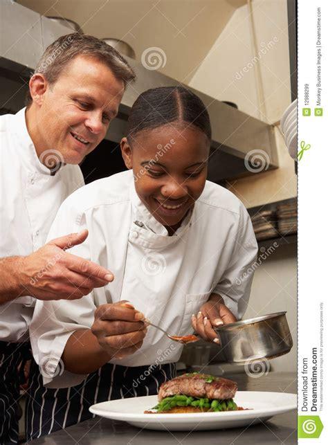 le chef cuisine chef instruisant le stagiaire dans la cuisine de