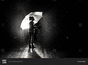 A little girl holds an umbrella in pouring rain stock ...