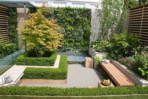 garden bench in small patio garden with plantings wall