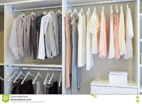 row  white dress  shirts hanging  wardrobe stock