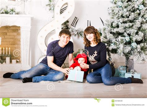 Christmas Family With Baby Opening Gifts. Happy Stock