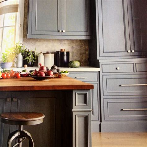 grey kitchen cabinets against light wood floor this