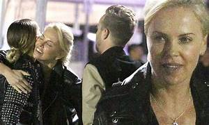 Charlize Theron shares a hug with Aaron Paul and wife ...