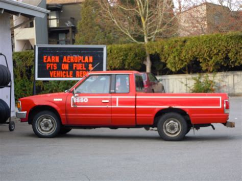 old nissan truck old red nissan pickup truck at gas station free images