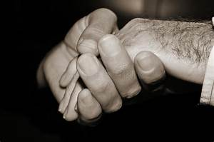 Young Man Holding The Hand Of An Old Man, In Black And ...