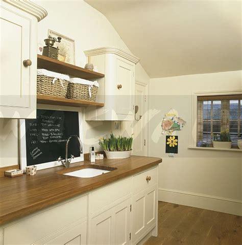 Kitchen Diner Ideas - image blackboard above sink in wooden worktop in kitchen ewa stock photo library