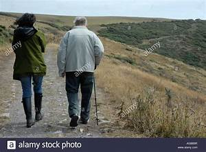 Rear view of two people walking together in the ...