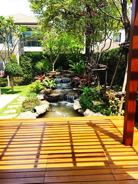 Thai Gardens by Tropical Rock Waterfall Pond And Shaded Deck In Bangkok