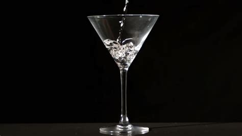 martini glass background water pouring into cocktail glass in slow motion stock