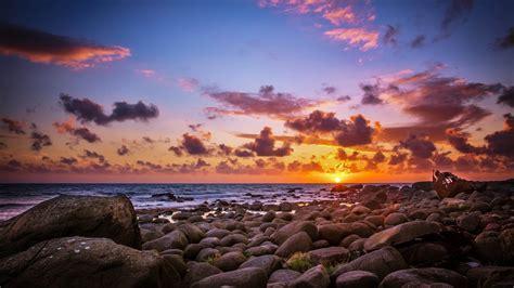 sun rays   horizon sea coast rocks  rocks