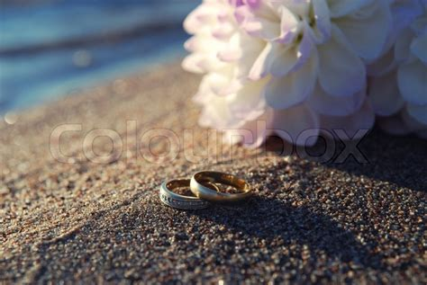 Gold Wedding Ring In The Sand Near The Water At The Beach. Tanzanite Engagement Rings. Baguette Round Diamond Wedding Rings. Black Purple Engagement Rings. Witchy Engagement Rings. Overlapping Engagement Rings. Zirconium Wedding Rings. Wall Sticker Rings. October 20th Wedding Rings