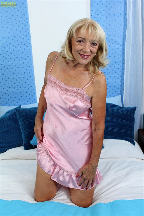 Horny GILF is lying naked and playing with a blue vibrator