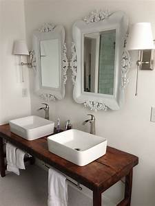 White bathroom with vessel sinks and wood table as vanity for Bathroom in middle of house