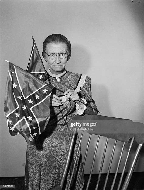 Irene Ryan holds up a pair of Confederate flags as Daisy